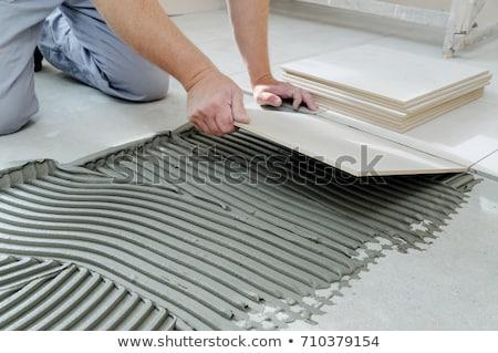 Tiler installing ceramic tiles on a floor Stock photo © tilo