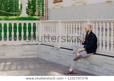Shot of clever male professor reads scientfic literature, prepares for lectures at university, poses Stock photo © vkstudio