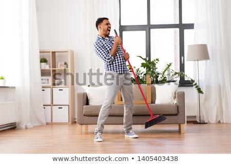 Uomo ginestra pulizia cantare home lavori di casa Foto d'archivio © dolgachov