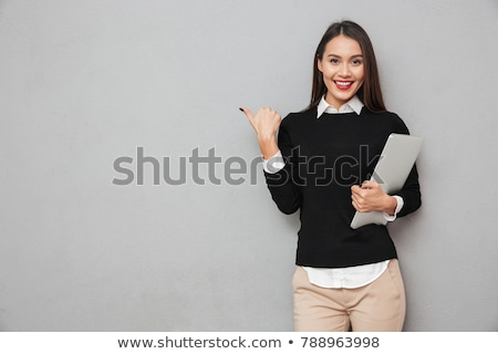 Cute young woman pointing at laptop stock photo © williv