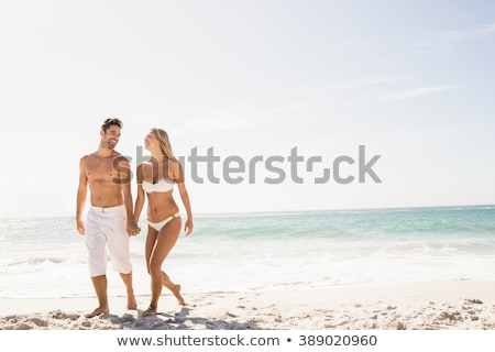 couple at the beach holding hands and walking sunny day bright stock photo © hasloo