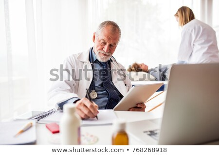 senior doctor in his surgery with nurse in background stock photo © photography33