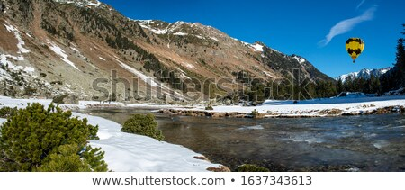 mountain landscape with snow and stream and hot air balloon flying in the sky stock photo © ajlber