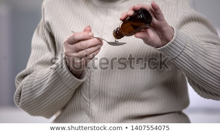 Stock photo: Senior woman taking cough syrup