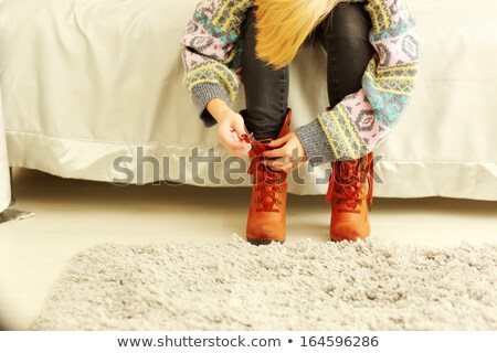 Woman taking off her boots at home Stock photo © deandrobot