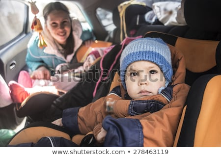 mom looking at her son in child safety seat stock photo © d13