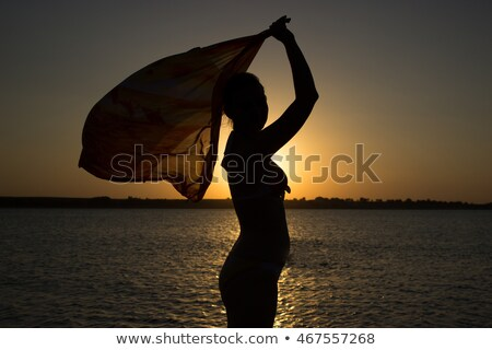 Evening on seashore. Silhouette of girl with handkerchief in his hands at sunset. stock photo © Paha_L