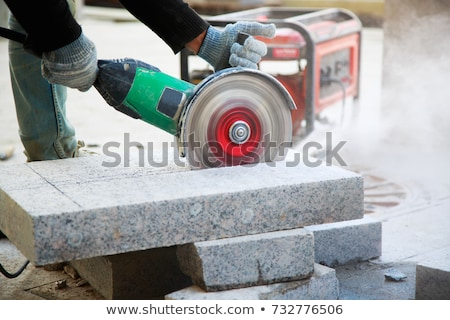 grinder worker cuts a stone stock photo © byrdyak