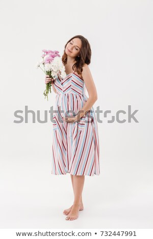 Cheerful pregnant woman holding flowers with eyes closed. Stock photo © deandrobot