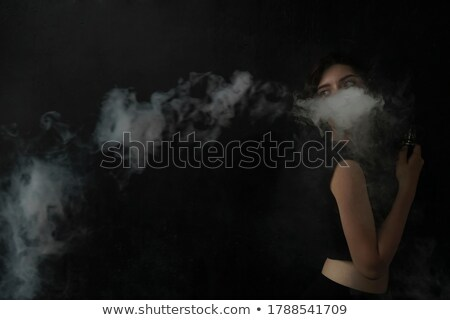 Attractive young woman vaping and blowing smoke on black Stock photo © LightFieldStudios