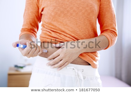 Diabetic woman injecting insulin Stock photo © phakimata