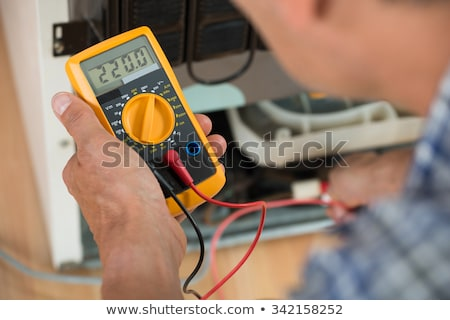 Male Repairman Checking Fridge With Digital Multimeter Stock photo © AndreyPopov