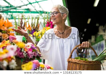 Charrming senior woman buying  flowers on  market Stock photo © boggy