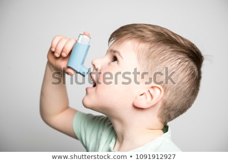 little boy using his asthma pump on studio white background Stock photo © Lopolo