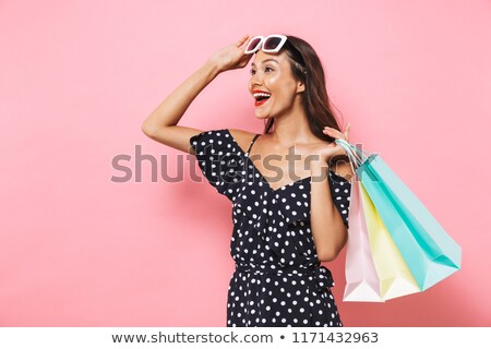 Happy brunette woman in dress holding packages and looking away Stock photo © deandrobot