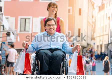 man in wheelchair being pushed by his friend on a shopping trip stock photo © kzenon