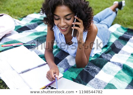smiling young african girl doing homework outdoors in park talking by phone stock photo © deandrobot