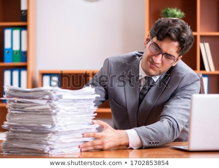 Young handsome employee unhappy with excessive work   Stock photo © Elnur