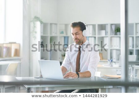 Young concentrated businessman in headphones typing on laptop keypad Stock photo © pressmaster