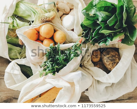 Fresh vegetables and fruits in eco cotton bags on table in the kitchen. Stock photo © Illia