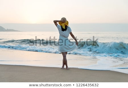 woman in summer dress standing on sand stock photo © fanfo