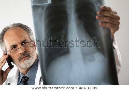 doctor looking at x ray and using cell phone stock photo © edbockstock