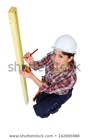 Stock photo: Tradeswoman using a measuring tape
