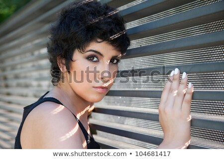 beautiful young woman, looking to camera, with sunbeam reflexion, against the wall, outside Stock photo © alexandrenunes
