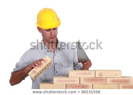 Mason making brick wall, studio shot Stock photo © photography33