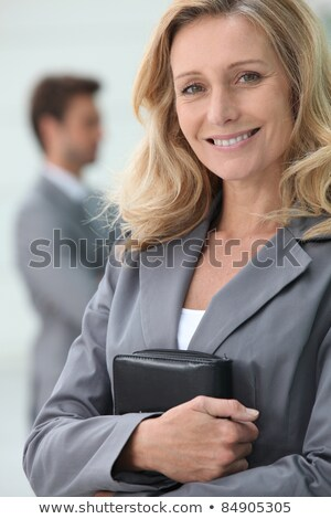 Smiling businesswoman holding personal organiser with colleague in background Stock photo © photography33