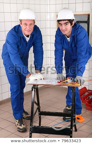 two skilled tradesman in blue jumpsuites watching a drawing Stock photo © photography33