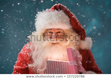happy santa claus opening his christmas gift at north pole stock photo © hasloo