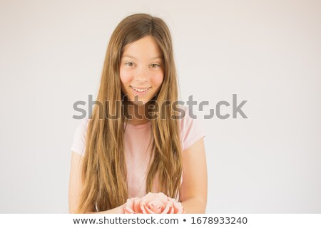 Stock photo: Young girl smiling with a flower