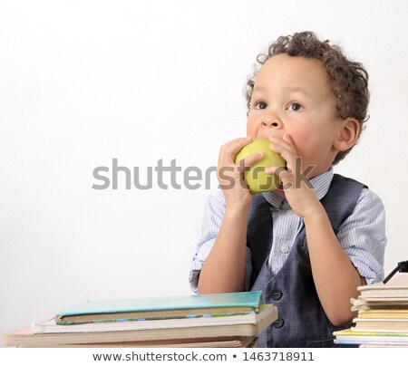 Male student biting apple and reading book Stock photo © deandrobot