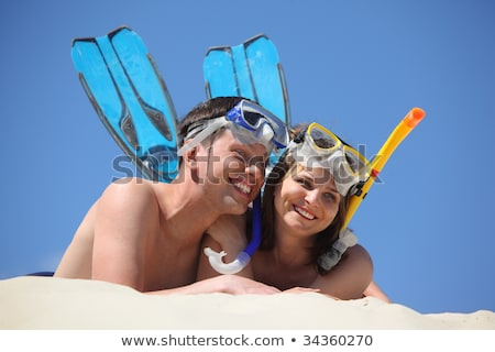 young pair in fins and underwater masks lies on sand Stock photo © Paha_L