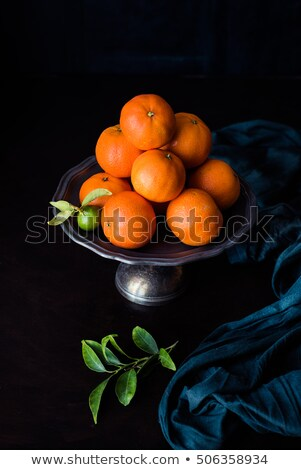unripe green mandarin with leaves on a metal plate; green cloth draped Stock photo © faustalavagna