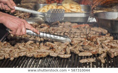 Grilling cevaps or kebabs on a grill at the street market Stock photo © smuki