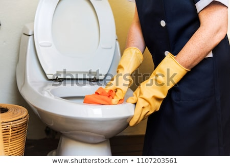 Cleaner in uniform cleaning toilet bowl. Stock photo © RAStudio