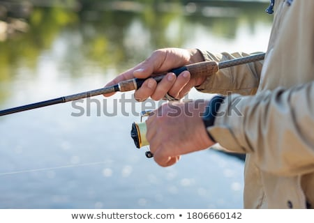 man holding fishing rod stock photo © zhekos