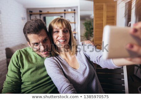 pretty lovely couple sitting on couch and making selfie stock photo © deandrobot