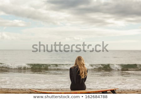 Blonde woman sitting on sand Stock photo © wavebreak_media