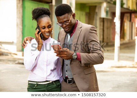 smiling african american businesswoman using mobile phone in off stock photo © boggy