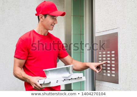 pizza delivery man carrying boxes using the intercom stock photo © kzenon