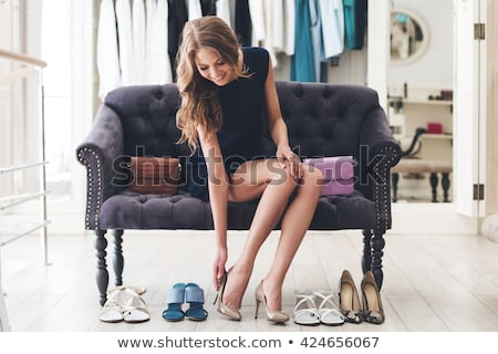 Stock photo: young woman trying high heeled shoes at store