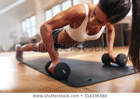 gym woman doing pushup exercise with dumbbell in a gym stock photo © boggy