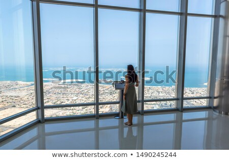 Girl tourist by the window of skyscraper of the Burj Khalifa in  Stock photo © dashapetrenko