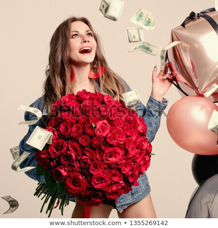 Funny woman laughing loudly while money falling around stock photo © studiolucky