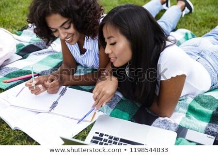 Koncentrált fiatal több nemzetiségű barátok lányok házi feladat Stock fotó © deandrobot