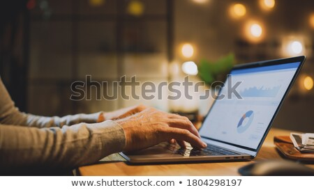man with charts on laptop screen at home Stock photo © dolgachov