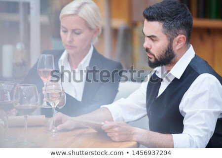 Young man with tablet and glass of white wine examining its characteristics Stock photo © pressmaster